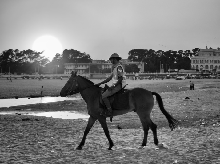 A cop from Horse Mounted Police battalion on his patrol, while Sun is setting opposite to the Marina Beach, Chennai, India.