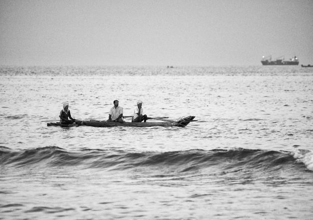 Fishermen on a wooden catamaran ride, Marina Beach, Bay of Bengal, Chennai, India