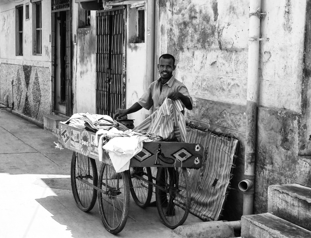 Iron(ing) man on his work, out in the streets with his push cart. The ironing is heated up by charcoals inside. Virudhunagar, India.