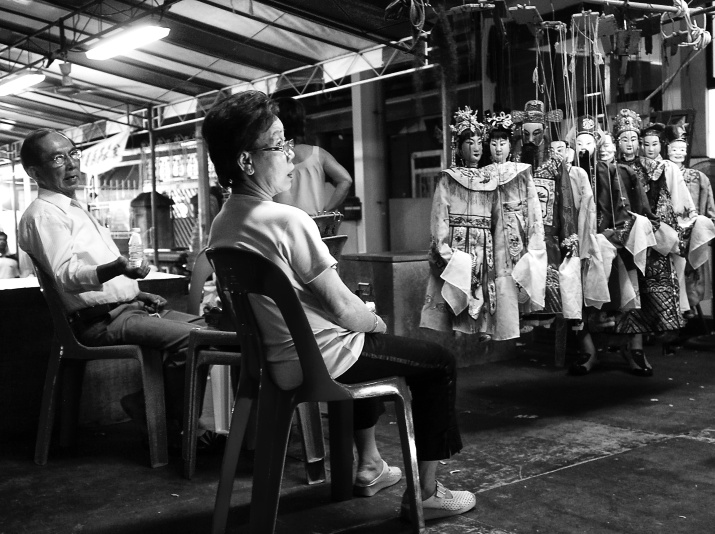 A puppeteer couple with their puppets, taking a break, Serangoon Road, Singapore