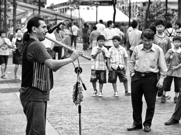 One busker is performing his music, playing his flute, in front of few spectators. Bugis Street, Singapore
