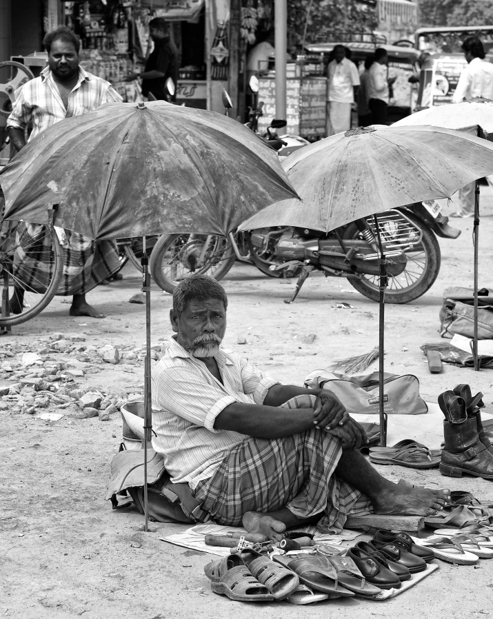 A shoemaker setup his workplace by roadside with an umbrella for shade from the Sun, Virudhunagar, India
