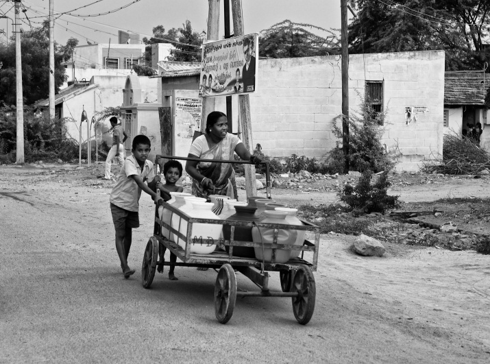 A mother and her kids taking water to their home in a push cart and plastic pots. Virudhunagar, India