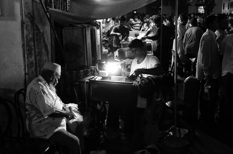A tailor is stitching a cloth in his sewing machine at night with another man assisting him. Bangla Bazar, Singapore