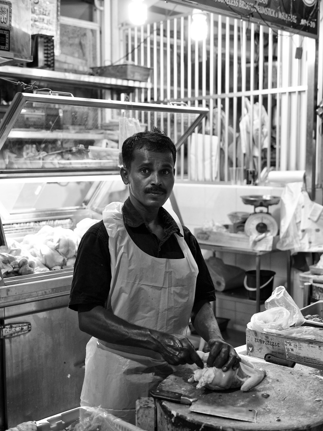 A butcher in wet market cutting up the chicken meat. Tekka Market, Singapore.