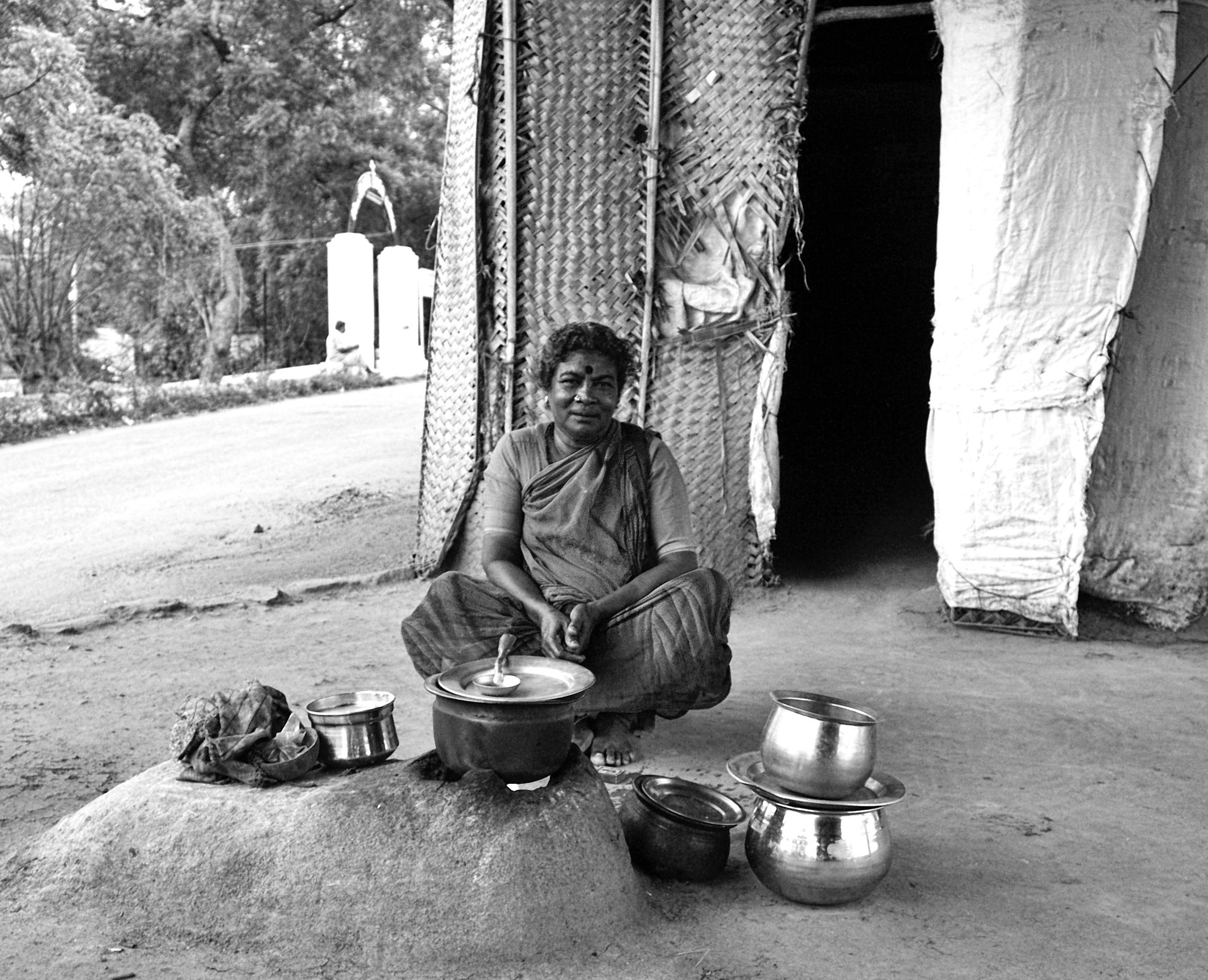 She had setup a small home under the flyover bridge with few thatches and cloths and preparing her evening meal. She got initially afraid thinking I was some enforcement officer. She was happy after I pacified her.