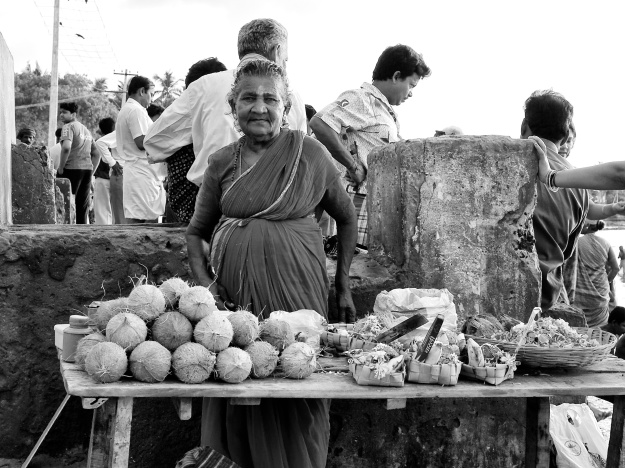 An old woman selling things like coconuts, flowers and incense sticks for puja and rites. Rameshwaram, Tamil Nadu, India