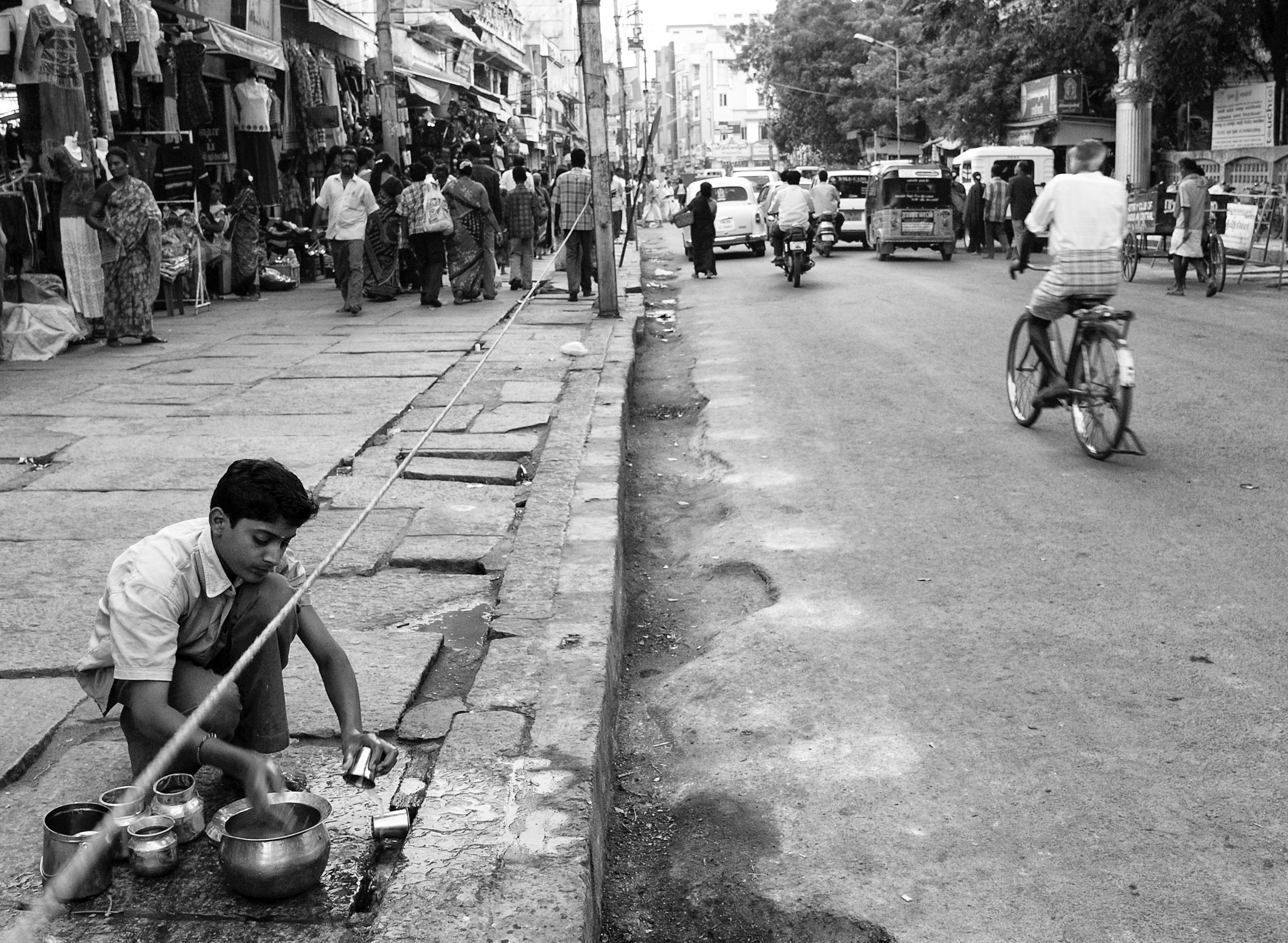 An young boy washing and cleaning the dishes along the road, Madurai, India