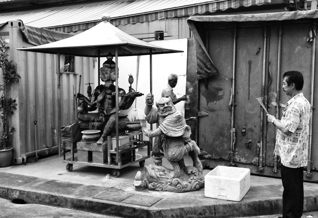 A worshipper offering incense sticks to the four-faced Brahma (Phra Phrom) God, beside with another demigod, at a makeshift temple by a lane side. Bugis Street, Singapore