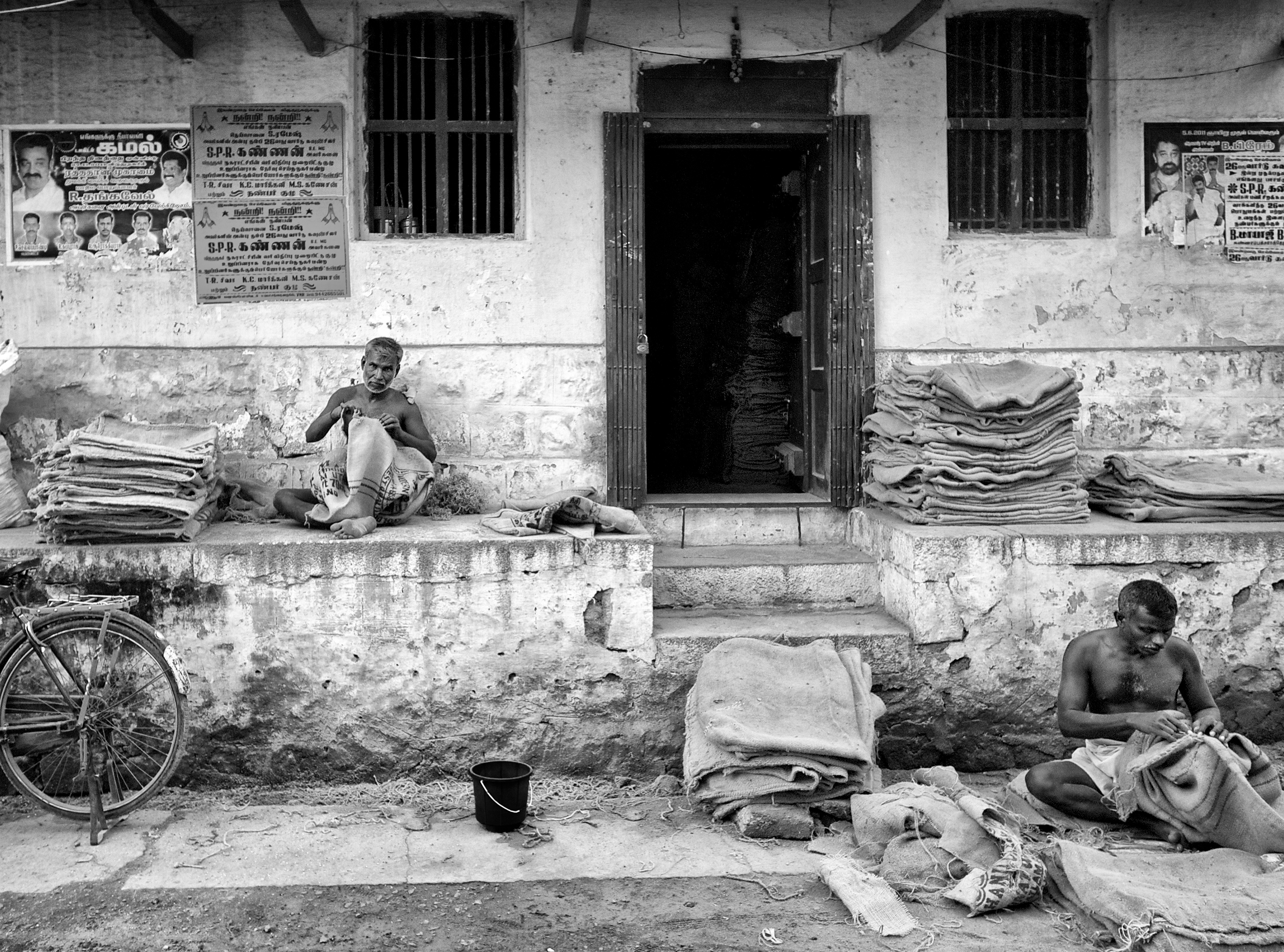 Workers patching up the jute sacks for reuse, in front of a warehouse. Virudhunagar, India