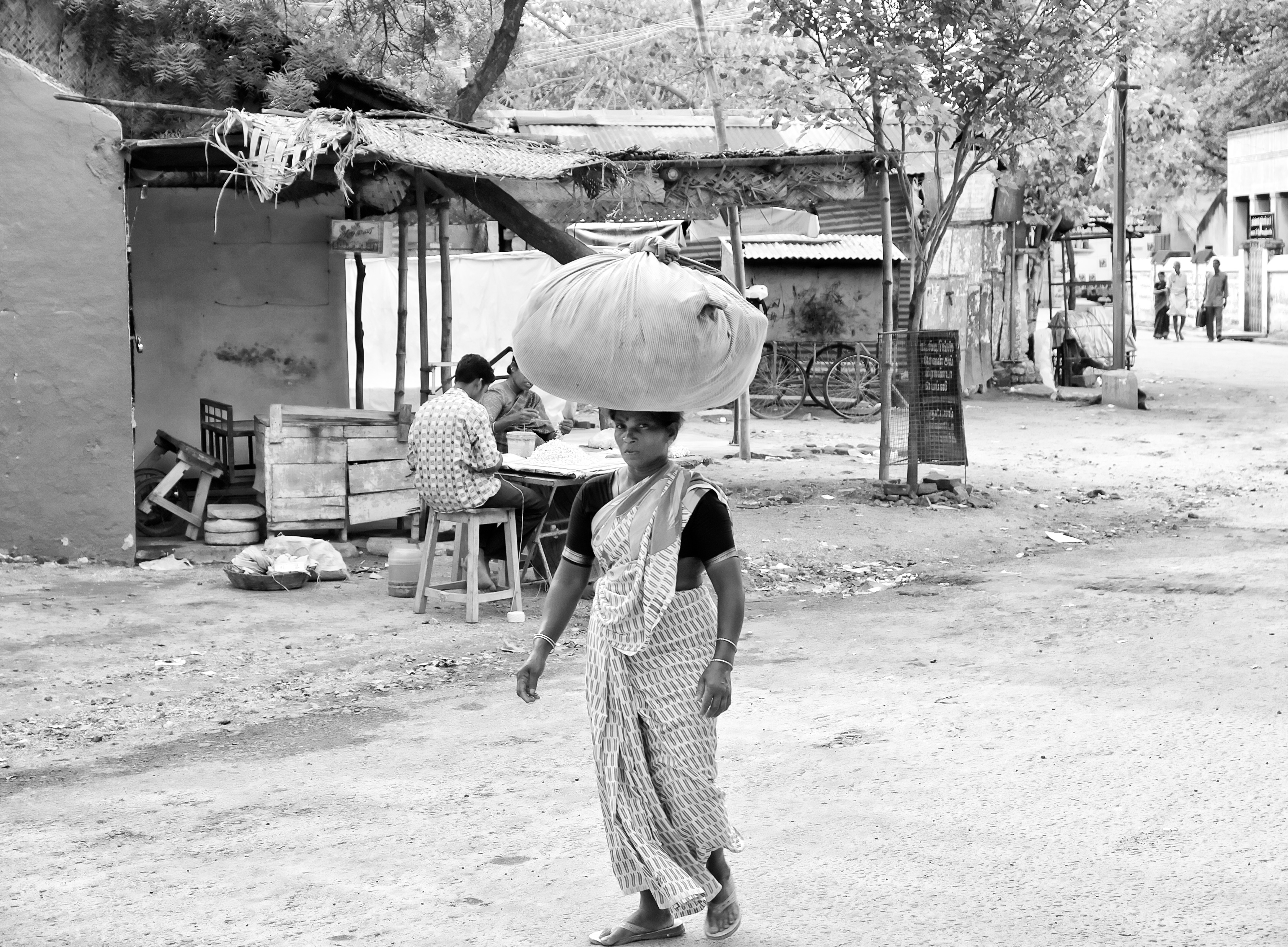 A washerwoman carrying a bundle of laundry to deliver to her customers' homes. Virudhunagar, India