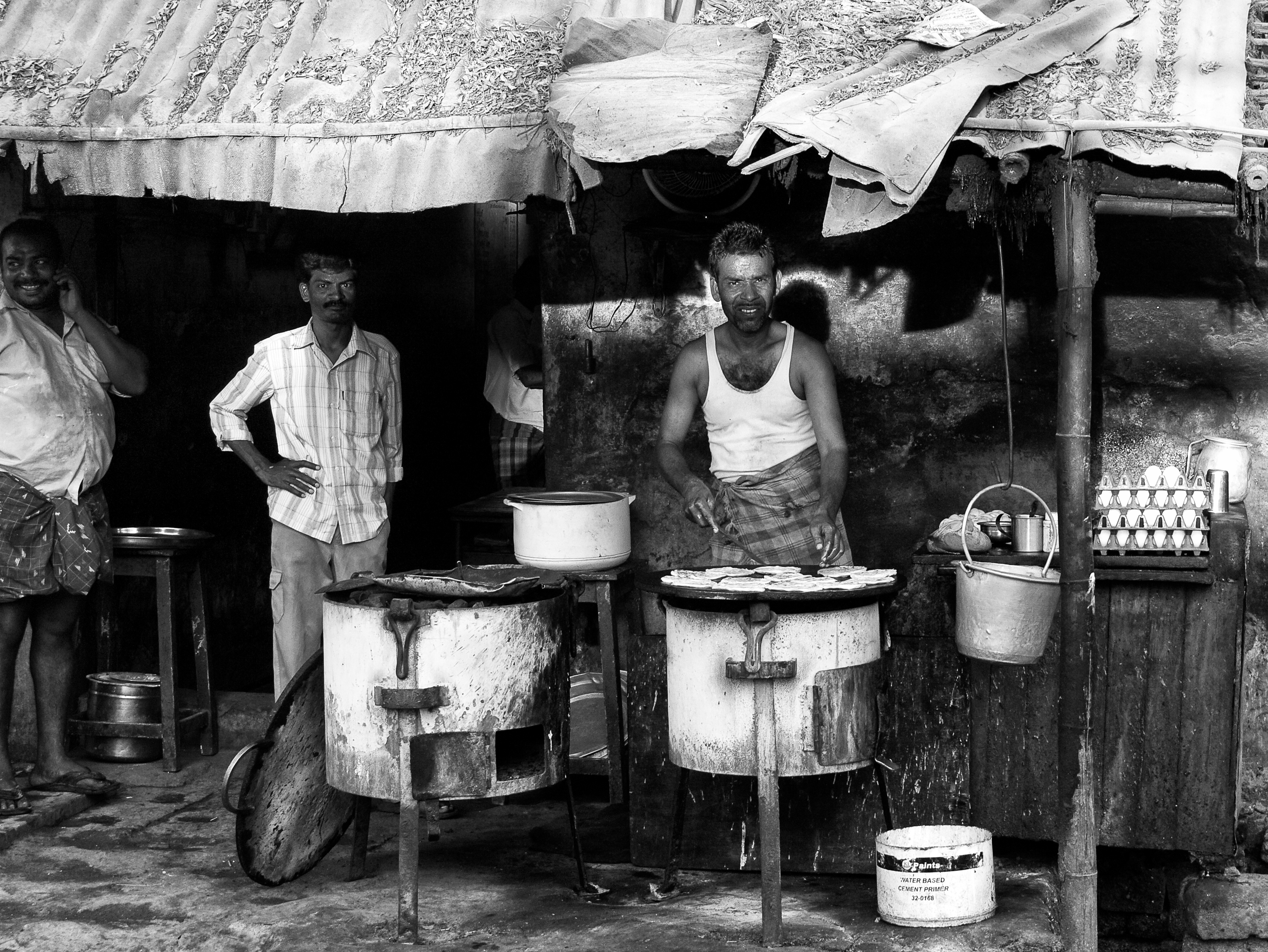 A cook frying parottas in the charcoal stove at a roadside food-stall. Virudhunagar, India.