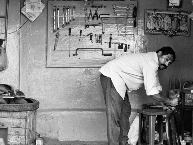 An auto mechanic at work in his workshop by the roadside, Madurai, India