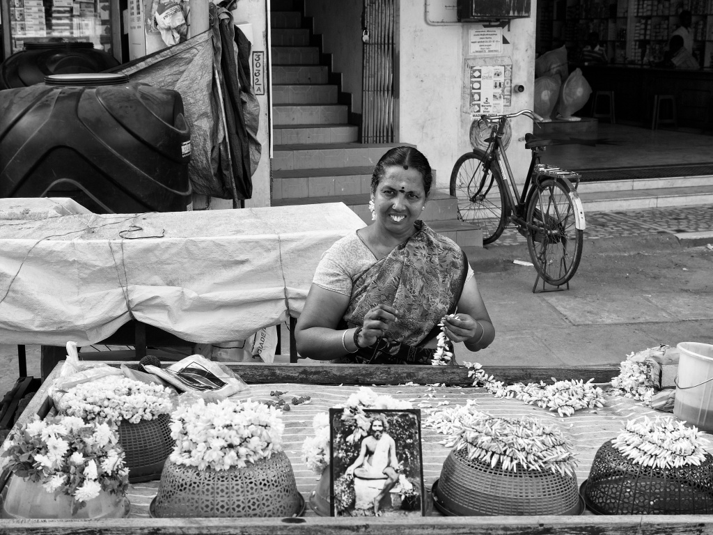 A woman, flower seller, making garlands in her mobile cart, Thanjavur, Tamil Nadu, India