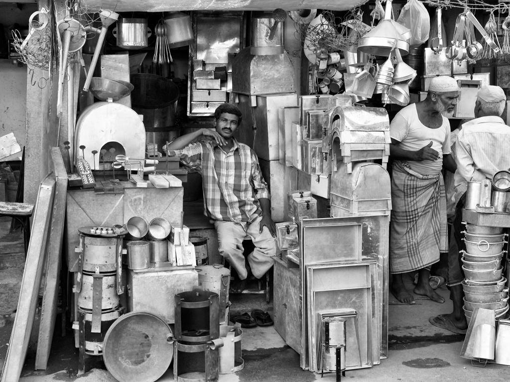 A shop keeper at a hardware shop that sells metal utensils,  Madurai, Tamil Nadu, India
