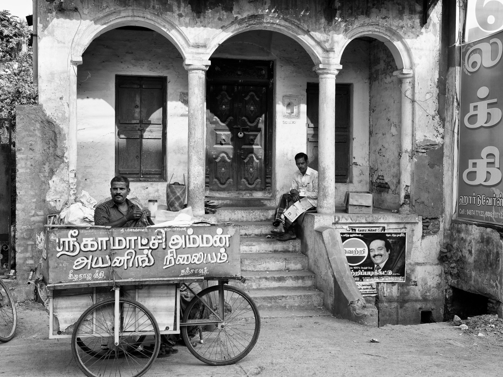 Iron(ing)man at work in his mobile cart, in front of an old building, Thanjavur, Tamil Nadu, India