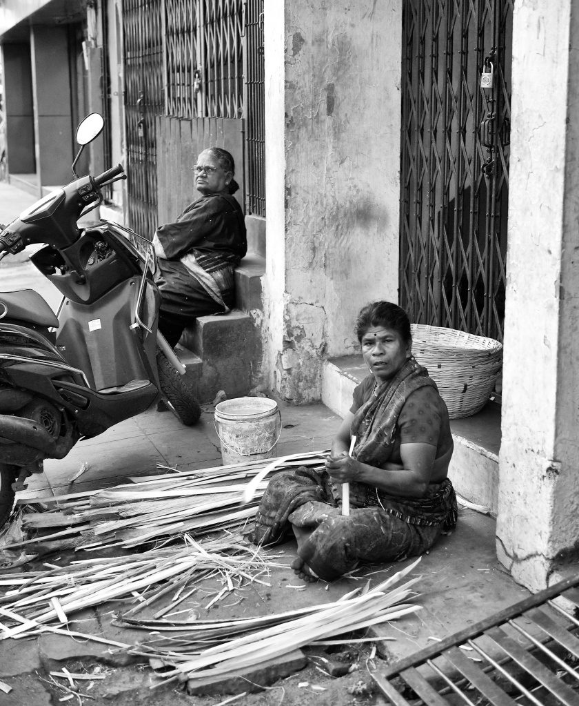 A woman begins to weave another basket, using bamboo strips, at a roadside platform, Madurai, India