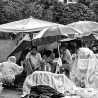 Street vendors are taking a break and at a conversation during a rain interruption, Jln Besar Flea Market, Pitt Street, Singapore