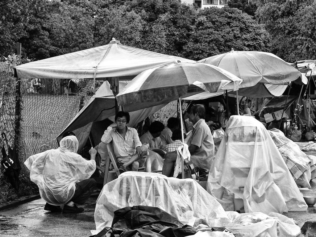 Street vendors are taking a break and at a conversation during a rain interruption, Jln Besar Flea Market, Pitt Street, Singapore