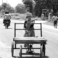 A woman construction worker on her way, pushing a cart to site. Virudhunagar, India