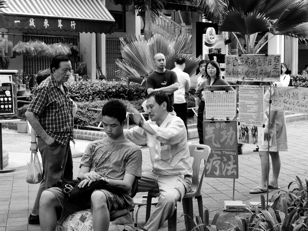 A Chi Kung therapist working on his young client by his street side workshop. Albert Street, Singapore