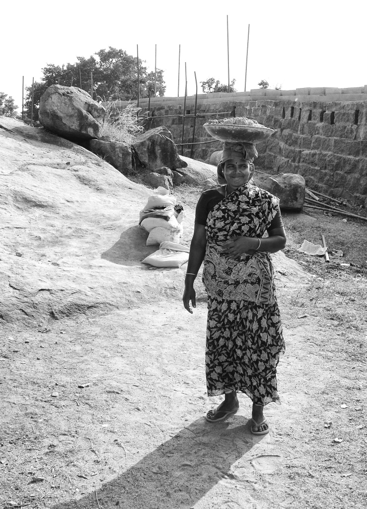 Woman construction worker carrying a basket of cement mix balanced on her head. Thirumayam fort, Pudukkottai, India