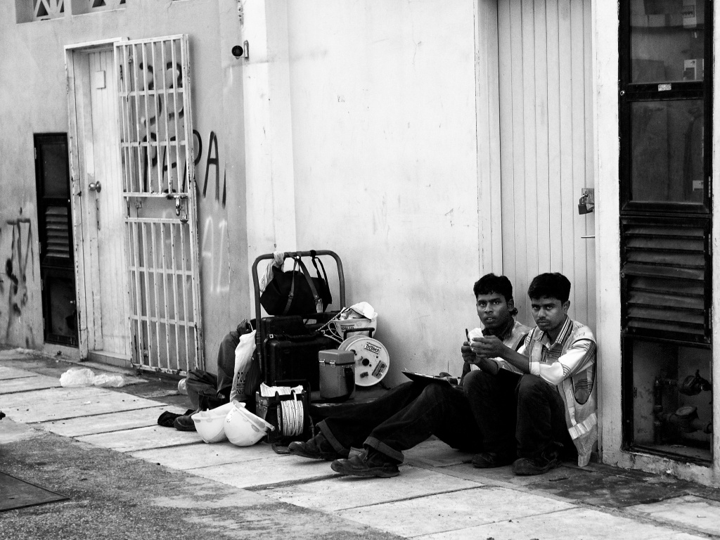 Technicians taking a break outside a construction site, by the street side. Rochar, Singapore
