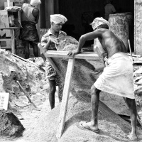 Two workers filtering out the stones from sand for the construction works, Virudhunagar, India.
