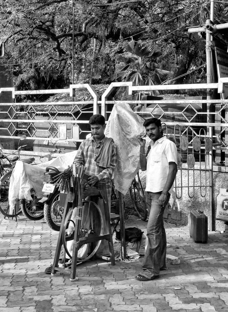 A street vendor sharpening a knife in his portable sharpening wheel, Madurai, India