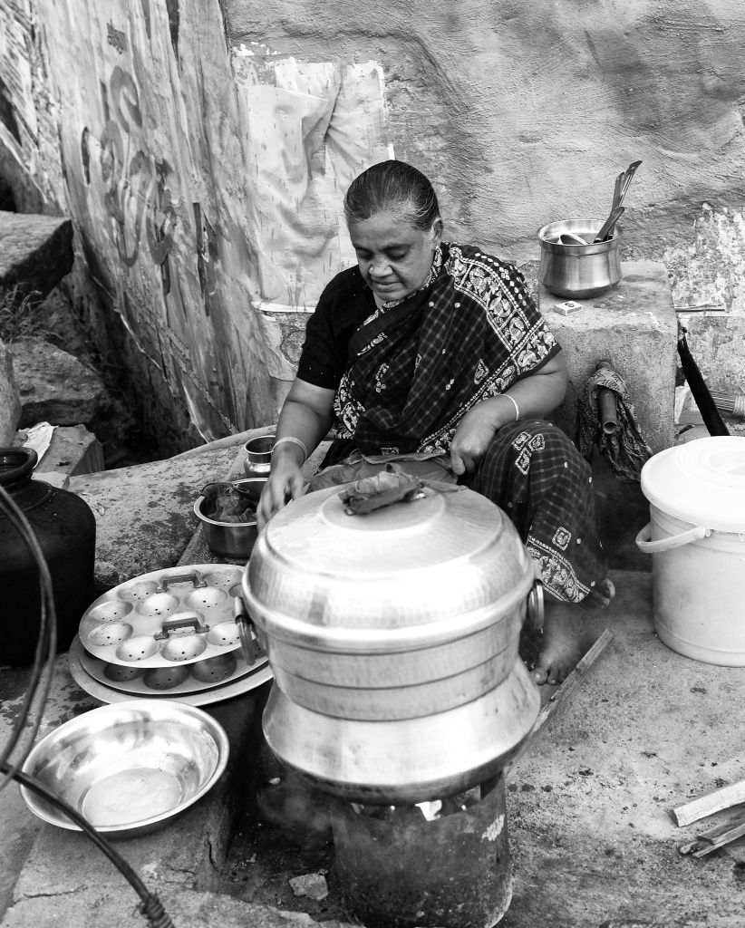 An woman setting up charcoal stove for an evening food stall, ready to make 'Idlis'. Virudhunagar, India