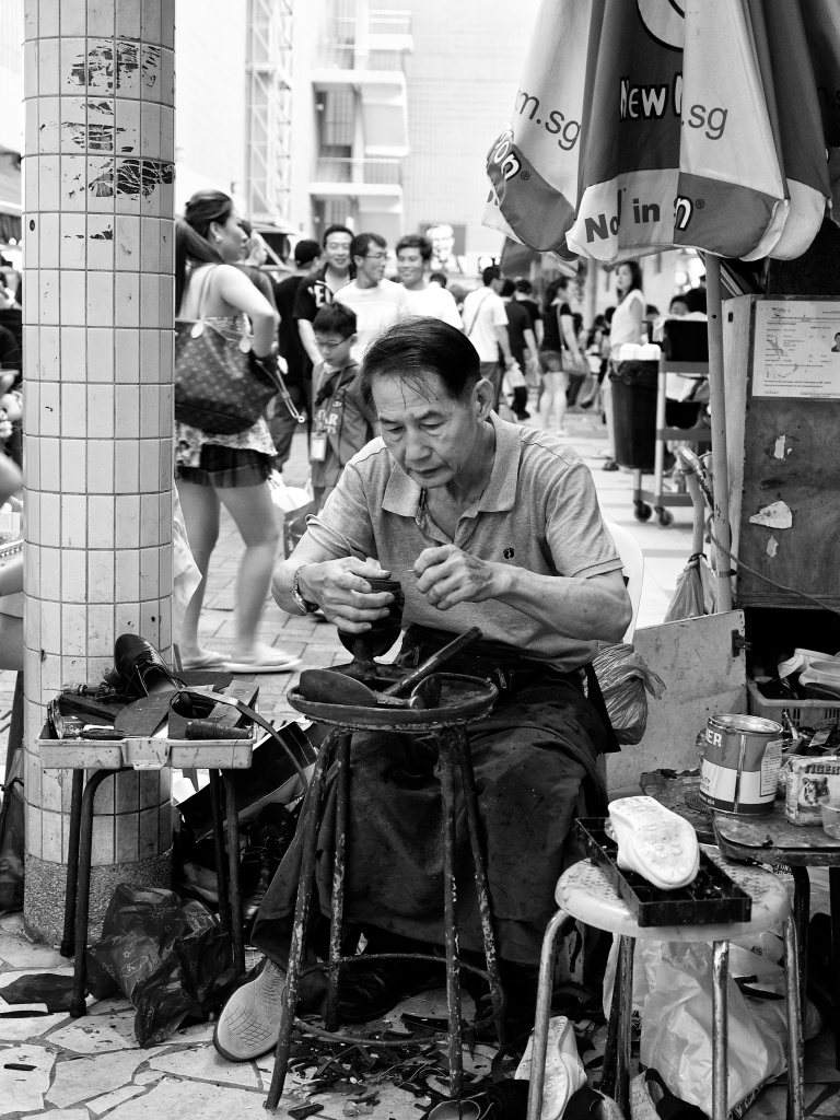 A shoe-repairman at work outside a hawker centre at People's Park Centre, ChinaTown, Singapore