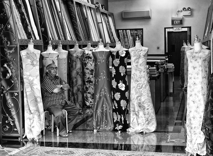 Textile shop owner in the company of his mannequins, Arab Street, Singapore