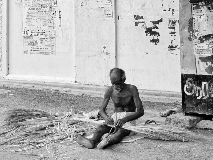An old man tying bunch of bristles and making brooms for sale by the roadside. Virudhunagar, India.