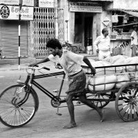 A worker handling his loaded tricycle in an ascending road. Madurai, Tamil Nadu, India.