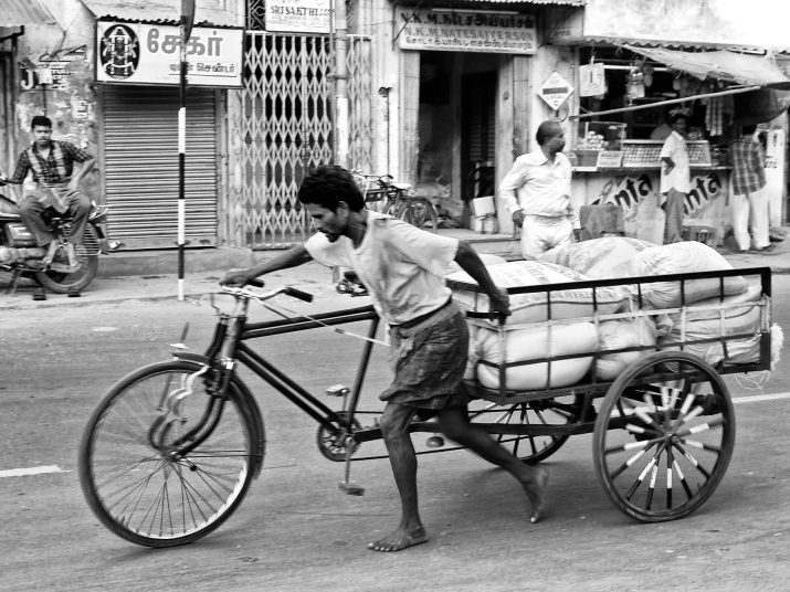 A worker handling his loaded tricycle in an ascending road. Madurai, India.