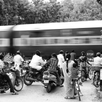 People are waiting as the train is passing through the railway crossing. Virudhunagar, Tamil Nadu, India.