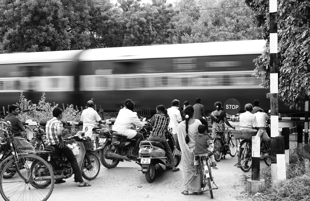 People are waiting as the train is passing through the railway crossing. Virudhunagar, India.