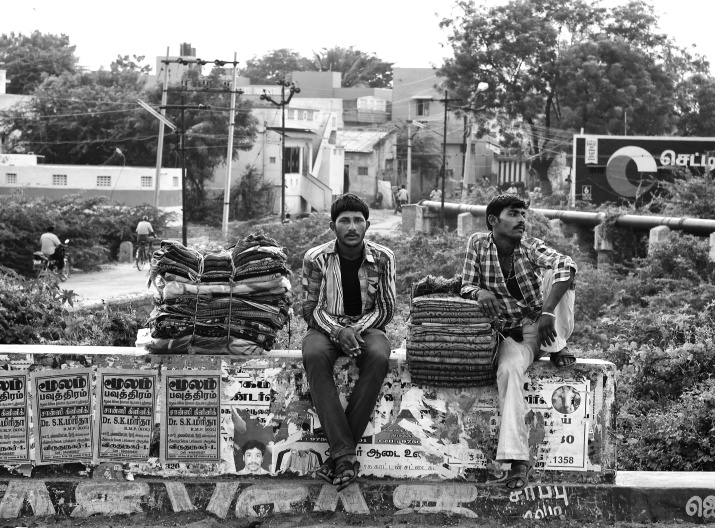 Young men, from northern india who travelled to southern states to sell blankets, are resting their heels on the road side. Virudhunagar, India
