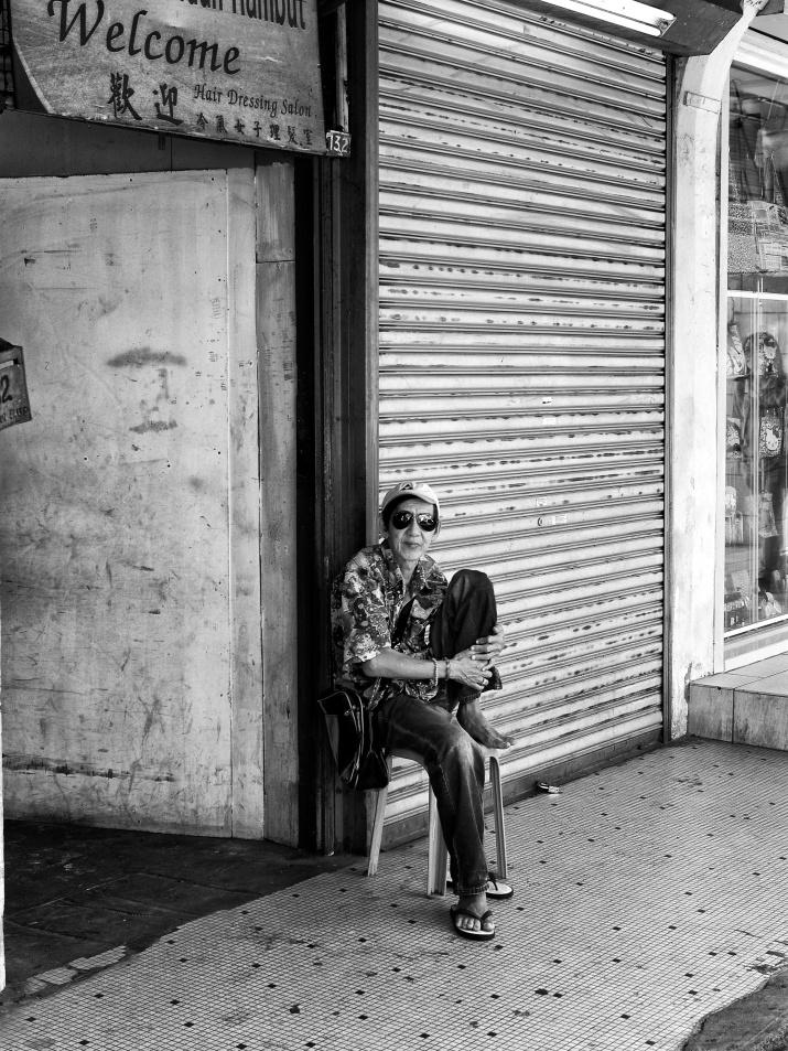 A front-door salesman looking for customers to his Salon. Jalan Petaling, Kuala Lumpur, Malaysia
