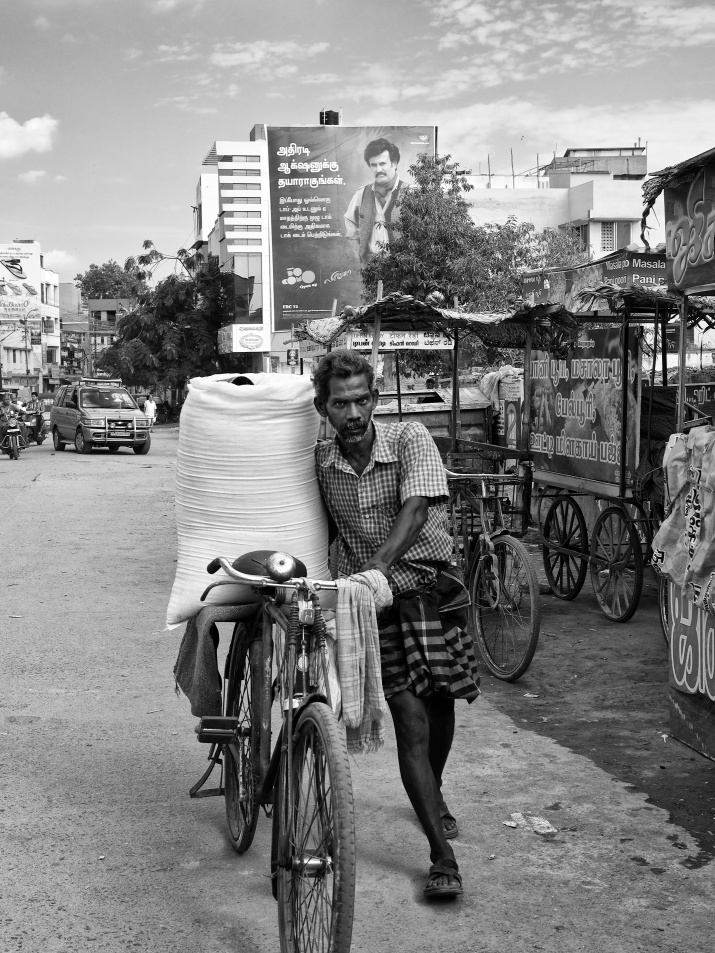 A street vendor on his way in his bicycle selling grainy salt, Madurai, Tamil Nadu, India