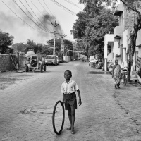 An young kid playing with a worn-out cycle tyre in the street, Virudhunagar, Tamil Nadu, India