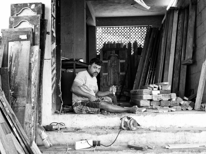 A carpenter at work in his street-side workshop, Madurai, Tamil Nadu, India