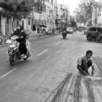 A worker setting right the rebars by the roadside, Madurai, Tamil Nadu, India