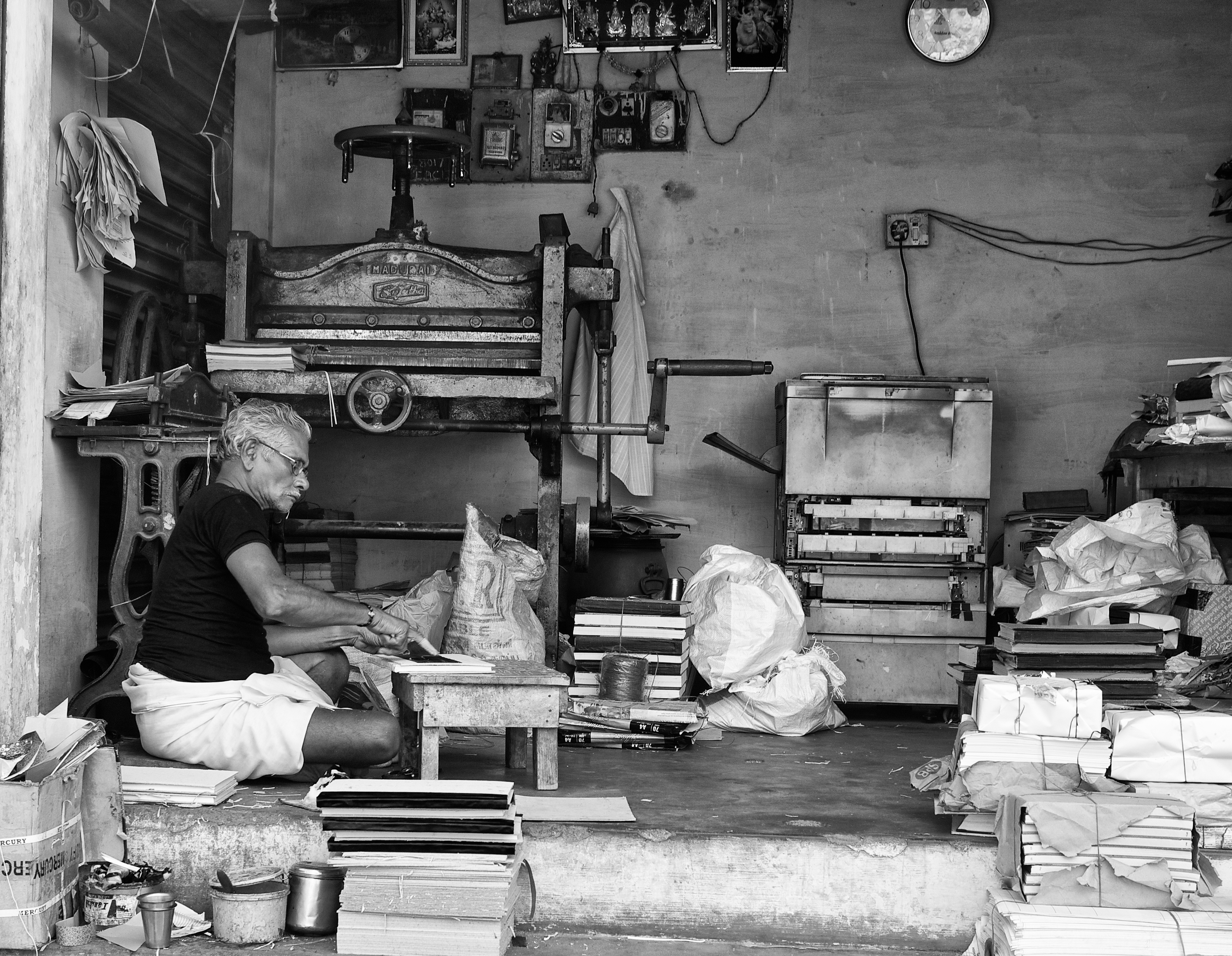 A shopkeeper at work in his bookbinding workshop,  Madurai, Tamil Nadu, India