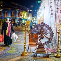Nataraja Statue on display and one woman walking by after her shopping, a street scene at Little India, Singapore