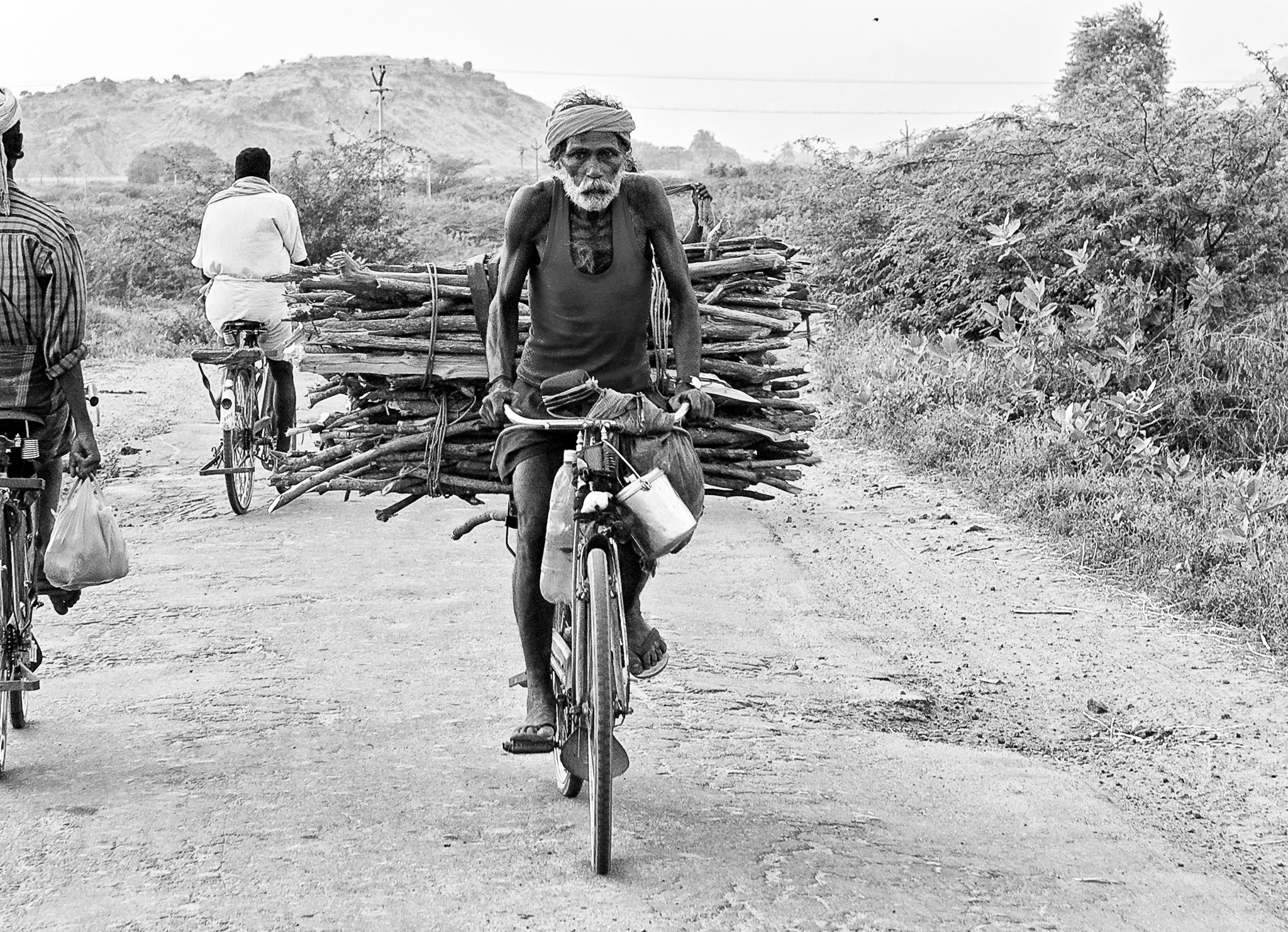 An old agricultural labourer on his way home from the field after a day's work, carrying firewood in his bicycle, T.Kallupatti, Tamil Nadu, India