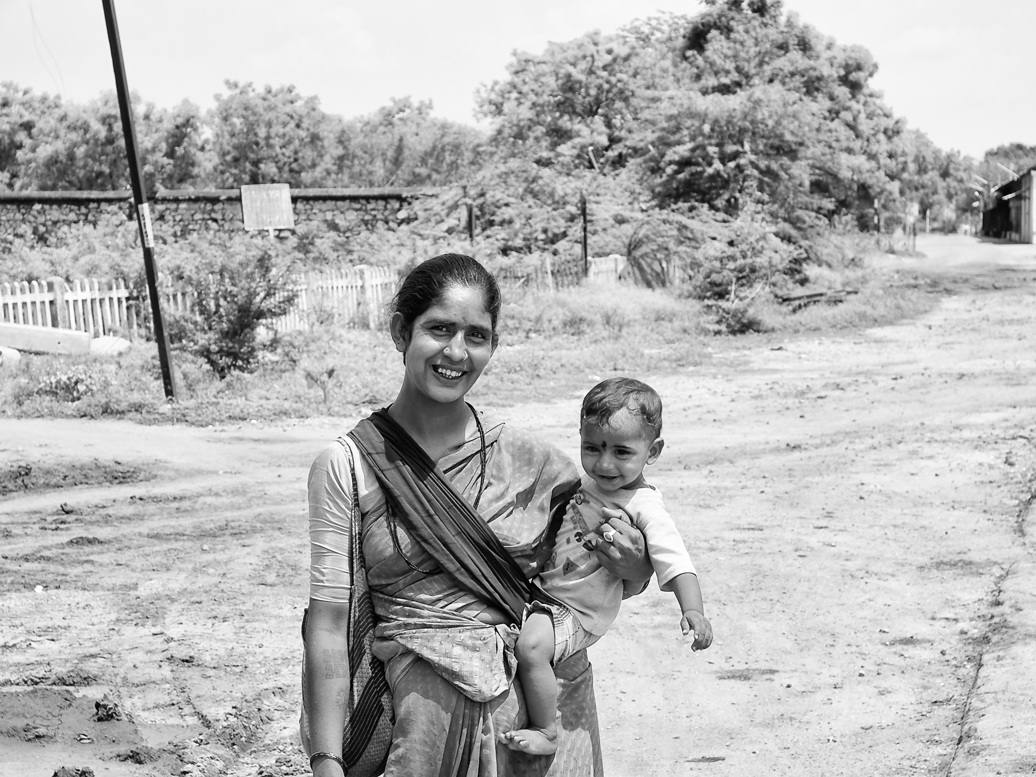 A mother with her baby, from a nomadic tribe, on her way to their tent near the Railway station, Virudhunagar,  Tamil Nadu, India