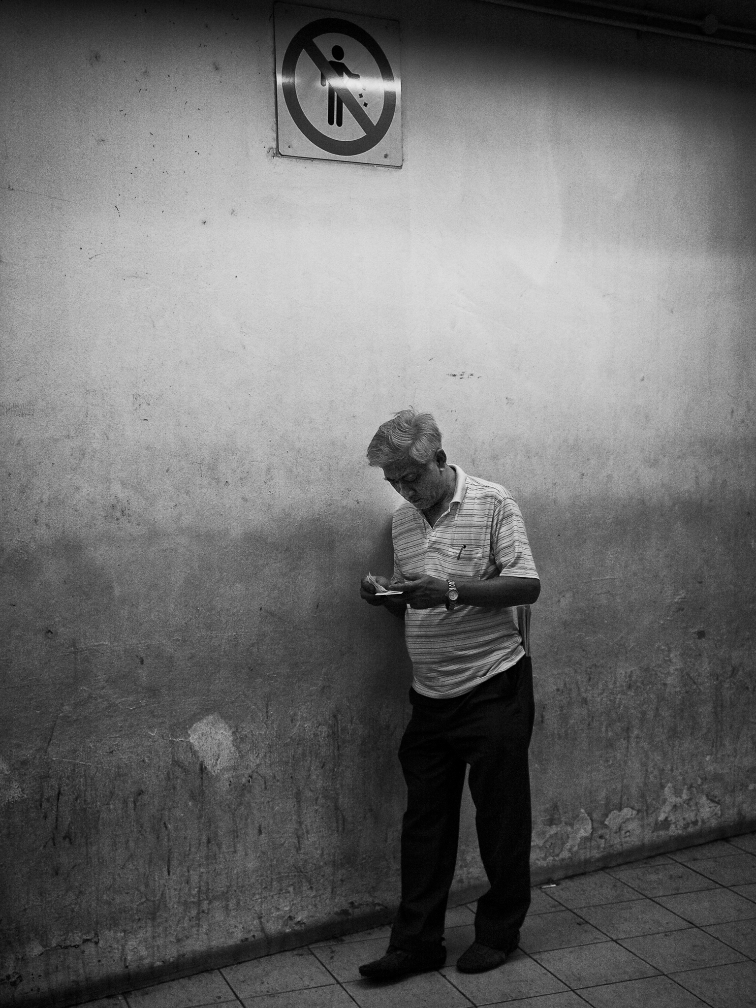 An old man going thro the 4D (lottery) tickets he had bought. Rochar Centre, Bugis, Singapore