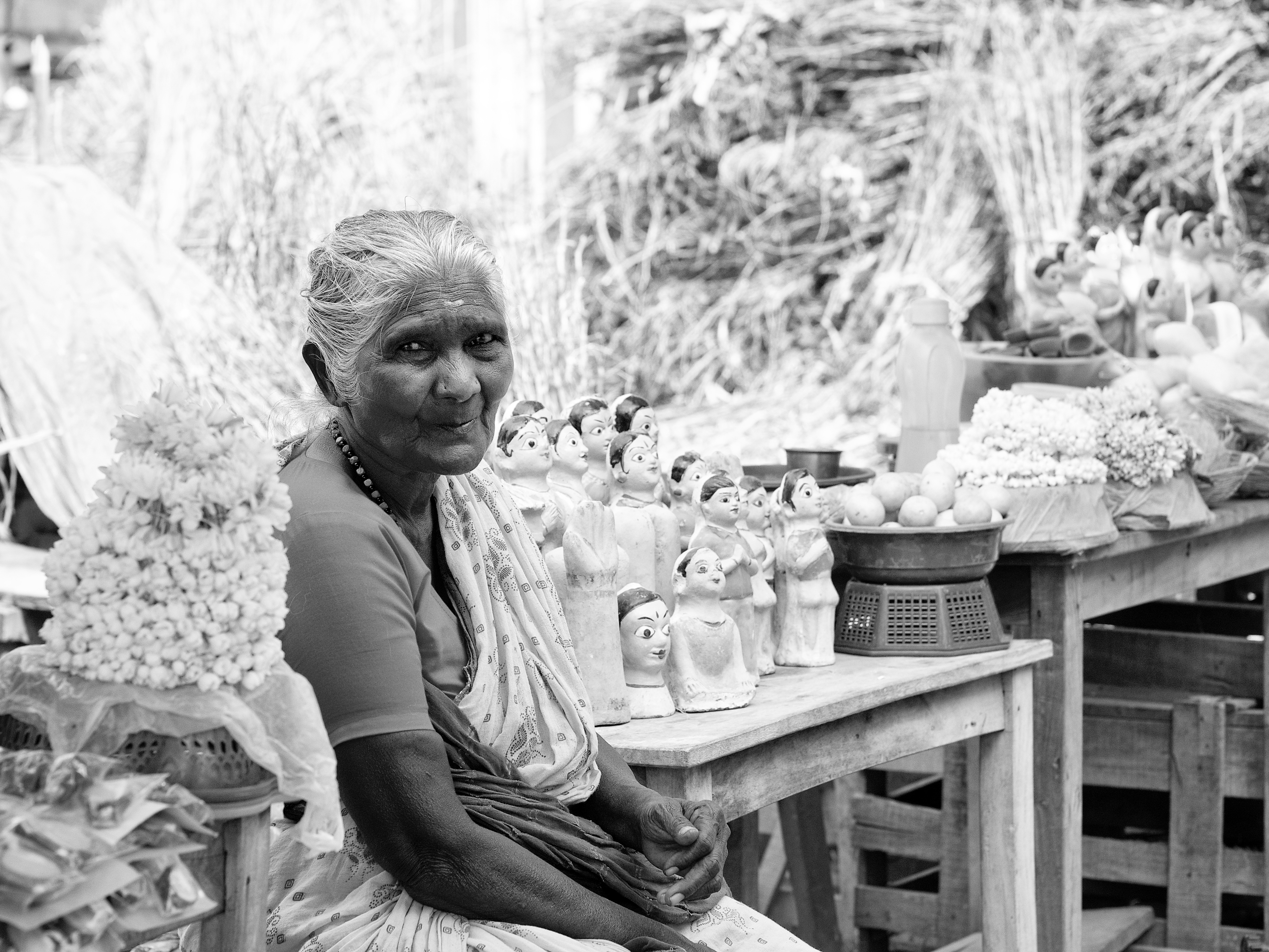 An old woman selling jasmine flowers, fruits and clay dolls in front of the temple. Virudhunagar, India