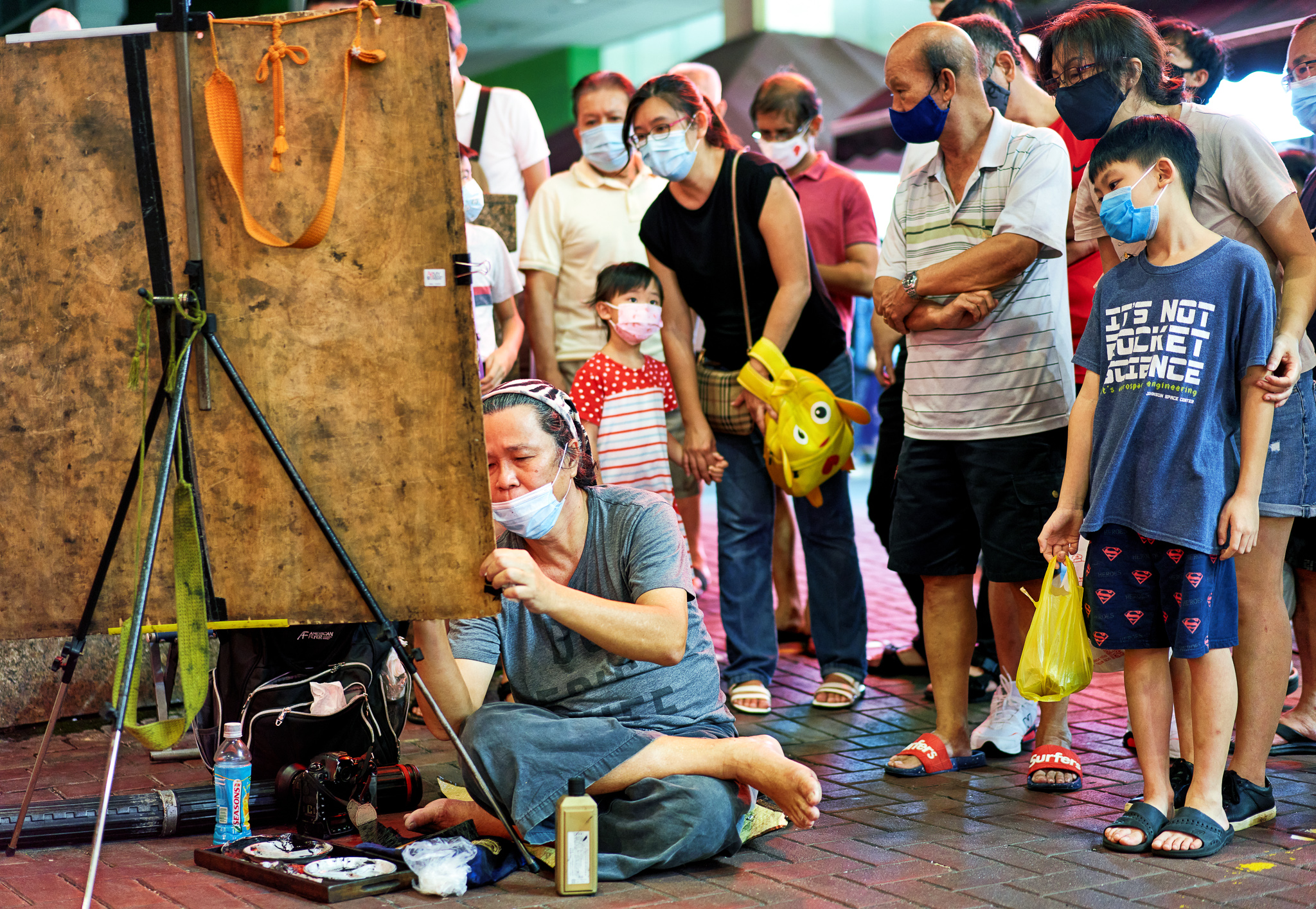 A painter immersed at his painting with curious onlookers around, China Town, Singapore